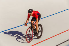 Young professional cyclist on a velodrome. Sports man in a red T-shirt and a black bicycle Stock Image