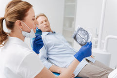 Young professional dentist identifying the diagnosis. It will take some effort. Distinguished clever focused doctor examining patients jaw scan and analyzing the Stock Photography
