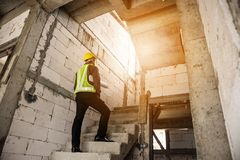 Professional engineer worker at the house building construction. Young professional engineer worker in protective helmet and blueprints paper on hand at the Royalty Free Stock Images