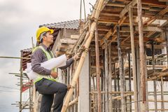 Professional engineer worker at the house building construction. Young professional engineer worker in protective helmet and blueprints paper on hand working on Royalty Free Stock Photos
