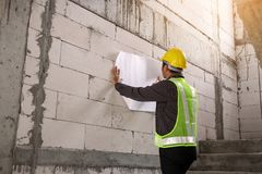 Professional engineer worker at the house building construction. Young professional engineer worker in protective helmet working at house building construction Stock Photos