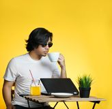 Young Professional Enjoying His Coffee While Working on Summer V. Acation Against Yellow Background Royalty Free Stock Image
