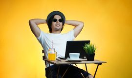 Young Professional Enjoying His Holiday While Working on Summer. Vacation Against Yellow Background Royalty Free Stock Photography