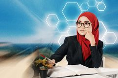 Young professional entrepreneur sitting and holding a pen while look at her left side. Creative ideas concept with abstract background, young professional Stock Photo
