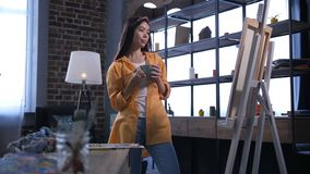 Happy female painter admiring artwork in workshop. Young professional female artist with cup of hot drink looking at her created artwork in cozy home studio stock video