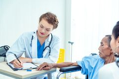 Young professional female doctor helping hands ,explaining diagnosis to senior man patient in medical office at hospital/ clinic . Young professional female stock image