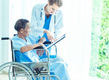 Young professional female doctor helping hands ,explaining diagnosis to senior man patient in medical office at hospital/ clinic . Young professional female royalty free stock photography