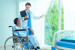 Young professional female doctor helping hands ,explaining diagnosis to senior man patient in medical office at hospital/ clinic . Young professional female stock photo