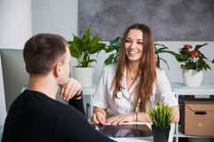 Young professional female doctor talking to patient at hospital. Consulting a sick man, making prescriptions. Health medicine diagnostics concept Royalty Free Stock Photos