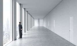 Young professional in formal suit is looking out the window. Empty modern bright clean interior of an open space office. Huge pano Royalty Free Stock Photos