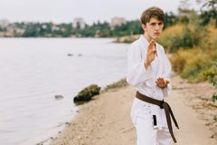 Sporty young man on the outdoors karate training. Boy in kimono on a natural background. Exercising concept. stock photos