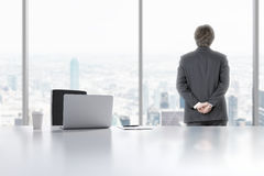 A young professional is looking out the window in the modern panoramic office in Manhattan, New York City. A laptop, notepad and a Stock Photo