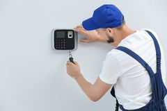Young male technician installing alarm system indoors royalty free stock image