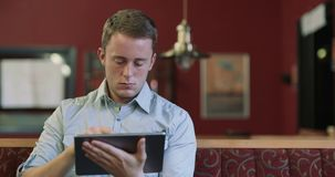 Young Professional Man in Coffee Shop / Cafe, Using iPad Computer Tablet. Portrait of a professional looking young man using an iPad style computer touchscreen stock video footage
