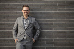 Young professional man projecting confidence against brick wall stock photos