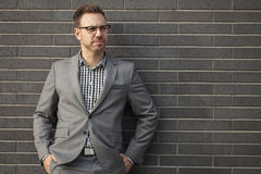 Young professional man projecting confidence against brick wall. Young professional in business attire projecting confidence against brick wall stock photos