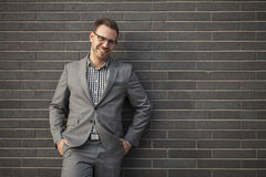 Young professional man projecting confidence against brick wall. Young professional in business attire projecting confidence against brick wall stock image