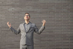 Young professional man projecting confidence against brick wall Stock Photography