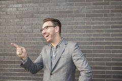 Young professional man projecting confidence against brick wall Stock Images