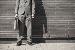 Young professional man projecting confidence. Young professional in business attire projecting confidence against brick wall royalty free stock photography