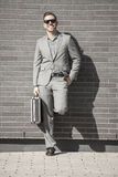 Young professional man projecting confidence. Young professional in business attire projecting confidence against brick wall stock photo