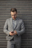 Young professional man projecting confidence while using mobile Royalty Free Stock Photo