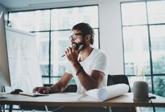 Young professional man wearing eye glasses working at modern loft studio-office with desktop computer.Blurred background Royalty Free Stock Photos