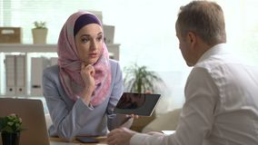 Young muslim business woman and caucasian man working with tablet in office stock video