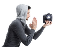 Young professional photographer prays for DSLR digital camera is. Young professional photographer in shirt prays for DSLR digital camera isolated on white Stock Image