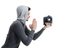 Young professional photographer prays for DSLR digital camera is. Young professional photographer in shirt prays for DSLR digital camera isolated on white Royalty Free Stock Image