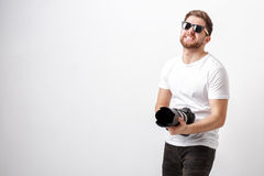 Young professional photographer in shirt holds heavy digital cam Royalty Free Stock Images
