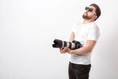 Young professional photographer in shirt holds heavy digital cam Royalty Free Stock Photos