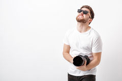 Young professional photographer in shirt holds heavy digital cam Stock Photo