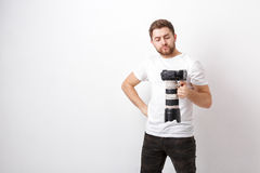 Young professional photographer in shirt holds heavy digital camera with long lens. hard work Royalty Free Stock Images