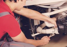 The plumber repairs the pipes. Male specialist plumber repairs. Royalty Free Stock Image