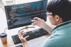 Young Professional programmer working at developing programming and website working in a software develop company office, writing. Codes and typing data code royalty free stock photo