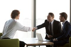 Young professional shaking hands with company HR manager. Business people sitting on couch during business meeting, side view young professional shaking hands stock photography