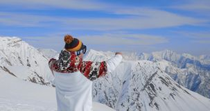 Young professional snowboarder on relax moment in french alps ski resort