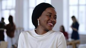 Young professional successful African entrepreneur woman wearing ethnic head wrap smiling modestly at modern office. stock footage