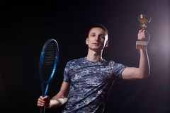 Young tennis player. Young professional tennis player holding a trophy, blue racket, black background Royalty Free Stock Image
