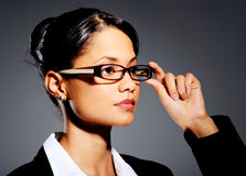Young professional touching her glasses Royalty Free Stock Photography