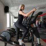 Young professional trainer woman in black sportswear in gym shoes is engaged on a stepper simulator in a fitness studio. Beautiful girl in training in a sport stock images