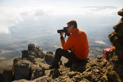 Young professional traveller man with dslr camera shooting outdoor fantastic mountain landscape. Hiker sits on a rock at. The high summit above clouds Stock Photography