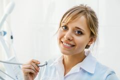 Young Professional Woman Dentist with Dental Drill. Young Professional Woman Dentist in the Office with Dental Drill Royalty Free Stock Images