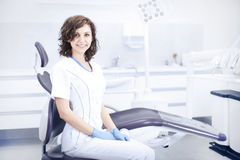 Young professional woman dentist in the dental office. Young professional woman dentist in the office on the background of the chair and dental accessories Stock Photography