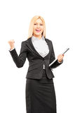 Young professional woman holding a clipboard and  gesturing happ Stock Image