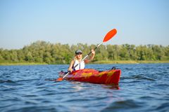Young Professional Woman Kayaker Paddling Kayak on River under Bright Morning Sun. Sport and Active Lifestyle Concept Royalty Free Stock Image