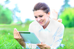 young professional woman laying down on green grass in a city park Royalty Free Stock Photos