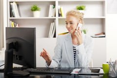 Young professional woman at office. Portrait of young businesswoman sitting at office in front of compter and working online while making call Stock Images