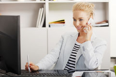 Young professional woman at office. Portrait of young businesswoman sitting at office in front of compter and working online while making call Royalty Free Stock Image
